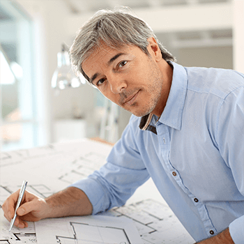 Middle aged man working on his floorplans looks at camera