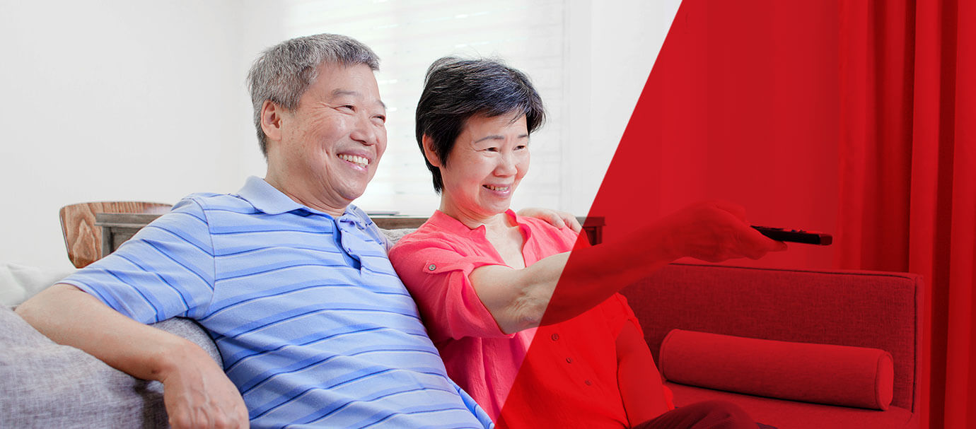 Senior Asian couple sitting on a couch smile while using a remote control