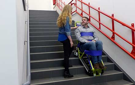 Woman helps a man down the stairs using the Evacutrac evacuation chair