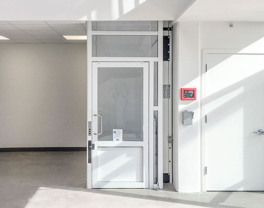 Genesis enclosure model vertical platform wheelchair lift with swinging hall door
