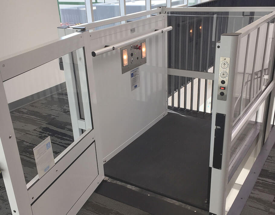 Genesis enclosure model vertical platform wheelchair lift with open swinging hall door