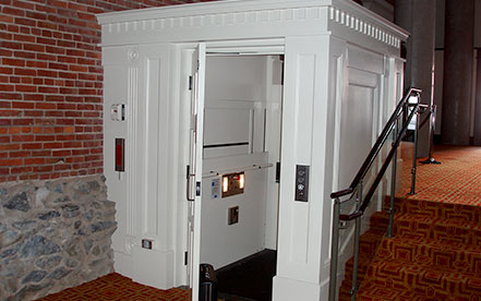 Genesis shaftway model vertical platform lift for wheelchairs built in a white shaftway
