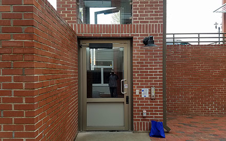 Genesis shaftway model vertical platform lift for wheelchairs built into a red brick shaftway