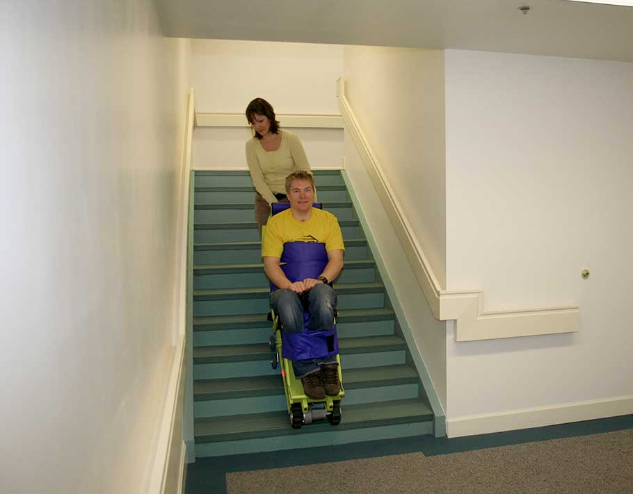 Man in yellow shirt gets helped down the stairs by a woman in a yellow shirt using the Powered Emergency Evacuation Chair