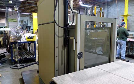 Genesis Staage vertical platform wheelchair lift in production at factory warehouse with worker in background