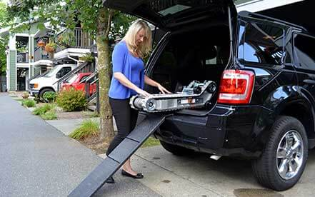 Lady in blue shirt removes Stair-Trac from the trunk of her van