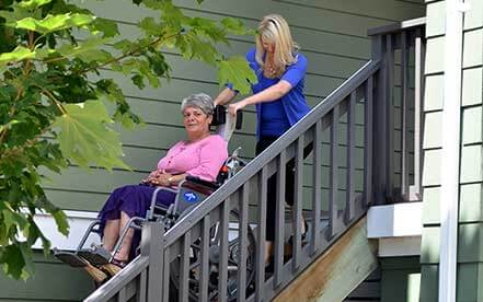 Senior in a wheelchair goes down the stairs using Stair-Trac with the help of a lady in a blue shir