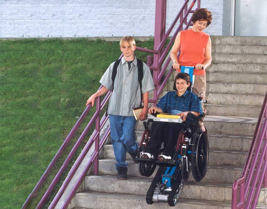 Teacher using a Stair-Trac to help a wheelchair bound student down the stairs alongside another young studen