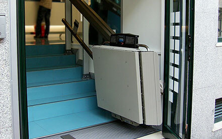 Inclined platform lift folded up to wall on a small stairlift
