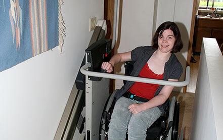 Smiling lady in a wheelchair uses a inclined platform lift