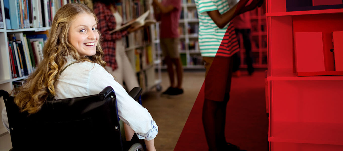 Young woman in wheelchair turns around and smiles inside a library
